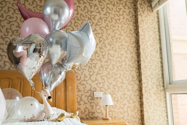 Palloncini natalizi e fenicottero giocattolo sul letto Foto Premium