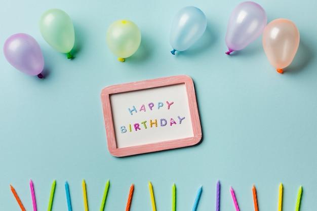 Palloncini sopra la cornice di buon compleanno con candele colorate su sfondo blu Foto Gratuite