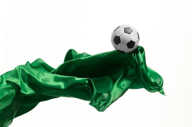 Pallone da calcio e panno verde trasparente elegante liscio isolato o separato sul fondo bianco dello studio. Foto Gratuite