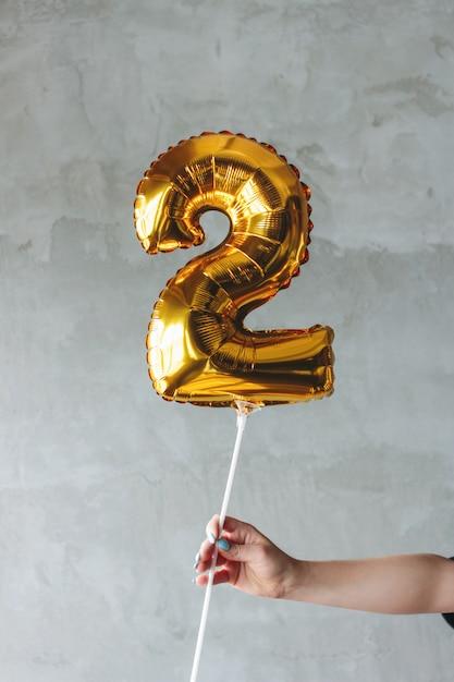Pallone numero due dell'oro in una mano femminile sulla parete grigia isolata Foto Premium