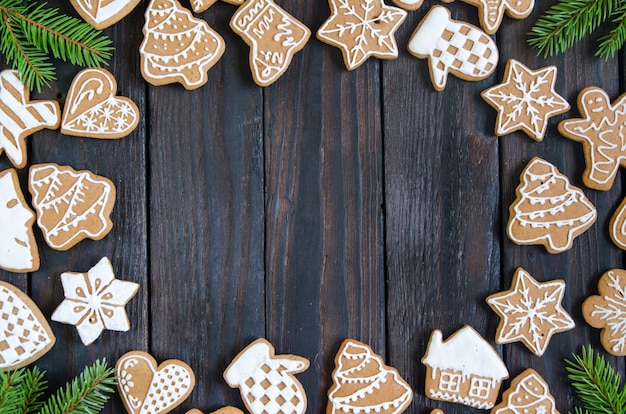 Pan di zenzero di natale di diversi tipi su uno sfondo di legno bianco e nero Foto Premium