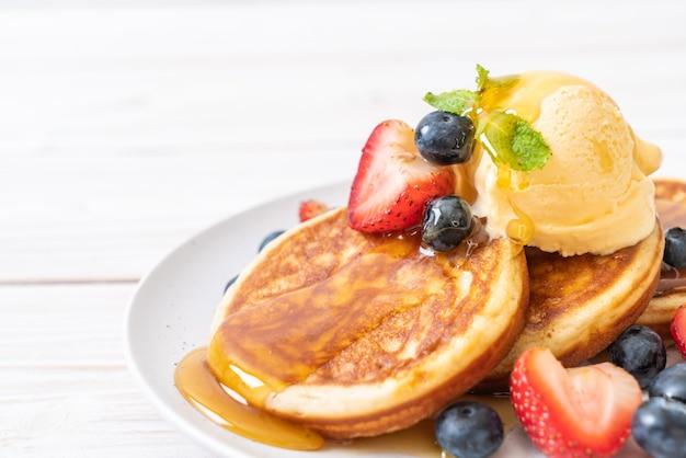 Pancake con mirtilli, fragole, miele e gelato alla vaniglia Foto Premium