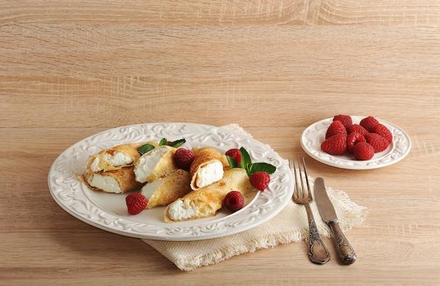 Pancake con ricotta e lamponi su un piatto Foto Premium