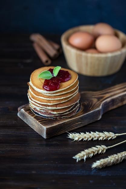 Pancake deliziosi con inceppamento e la menta su una tavola di legno scura Foto Premium