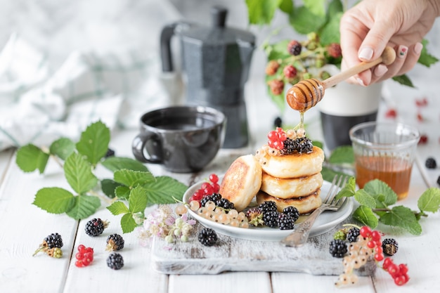 Pancake fatti in casa con frutti di bosco e sveglia su bianco in legno Foto Premium
