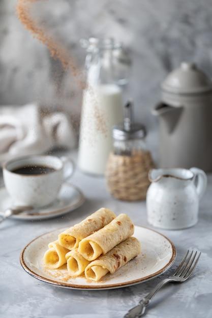Pancake impilati su un piatto su un tavolo bianco con una tazza di caffè e una bottiglia di latte Foto Premium