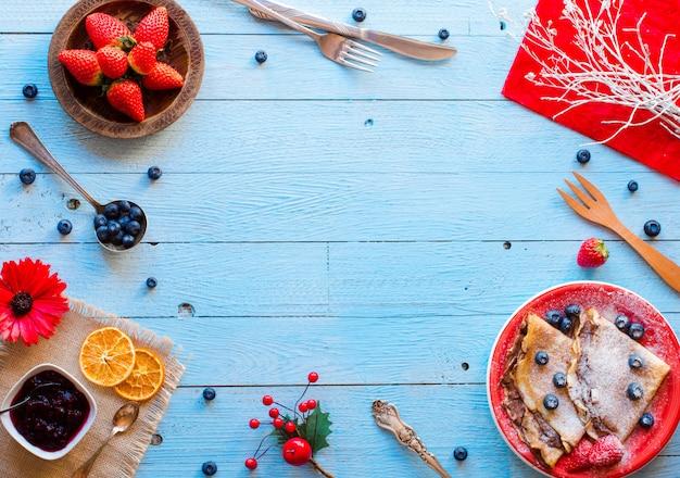 Pancake o crepes freschi delle fragole con le bacche e il cioccolato su fondo di legno blu Foto Premium