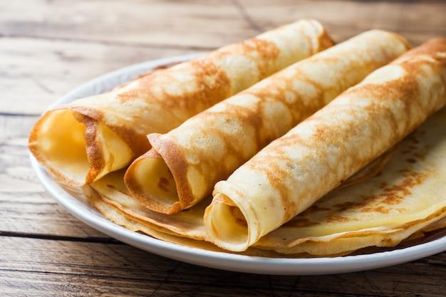Pancake sottili su un piatto. fondo in legno avvicinamento. Foto Premium