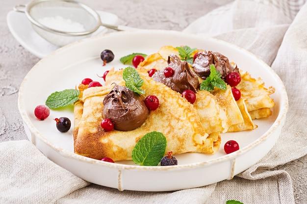 Pancakes con frutti di bosco e cioccolato decorati con foglie di menta. gustosa colazione Foto Premium