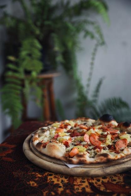 Pancetta e ananas di salsiccia di pizza su legno, pizza hawaiana Foto Premium
