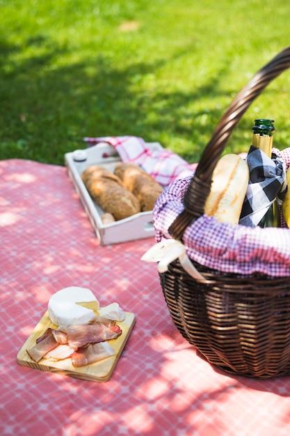 Pancetta e formaggio sul tagliere sopra il panno con cestino da picnic Foto Gratuite