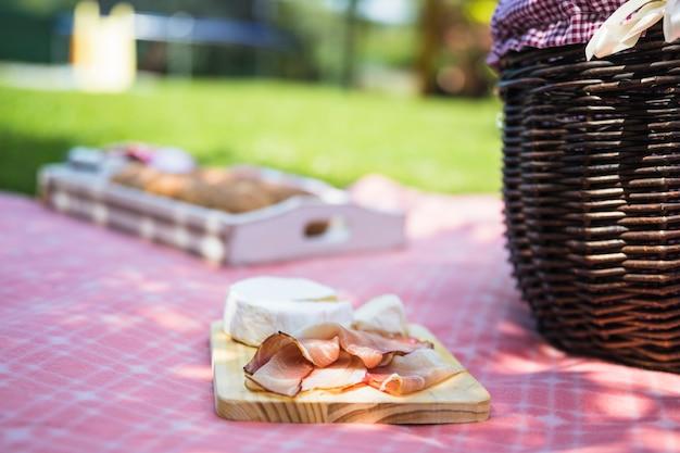 Pancetta e formaggio sul tagliere sopra il panno nel picnic Foto Gratuite