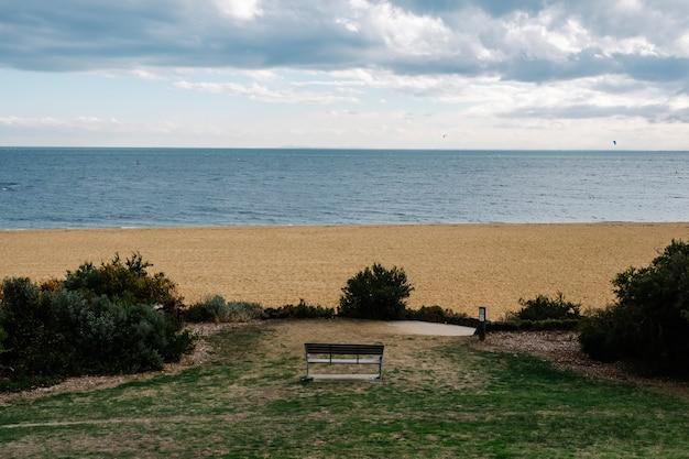 Panchina solitaria nel parco e mare e sabbia Foto Gratuite