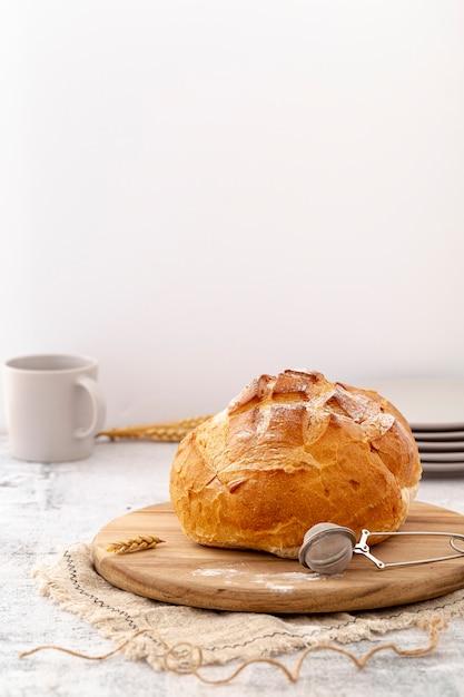 Pane al forno di vista frontale con grano sul bordo di legno Foto Gratuite