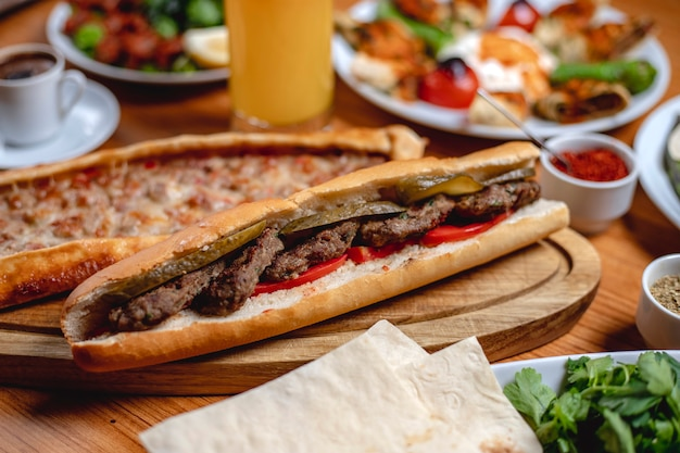 Pane bianco del panino di vista laterale con il pomodoro fresco delle cotolette della carne e il cetriolo marinato su un bordo Foto Gratuite