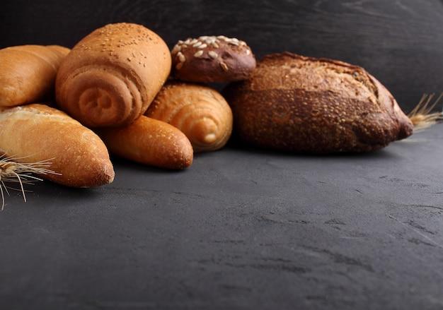 Pane bianco, grigio e di segale, baguette, rotolo con semi di sesamo su sfondo nero Foto Premium