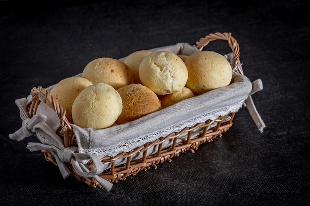 Pane brasiliano al formaggio fatto in casa, aka 'pao de queijo' in un cestino rustico. Foto Premium