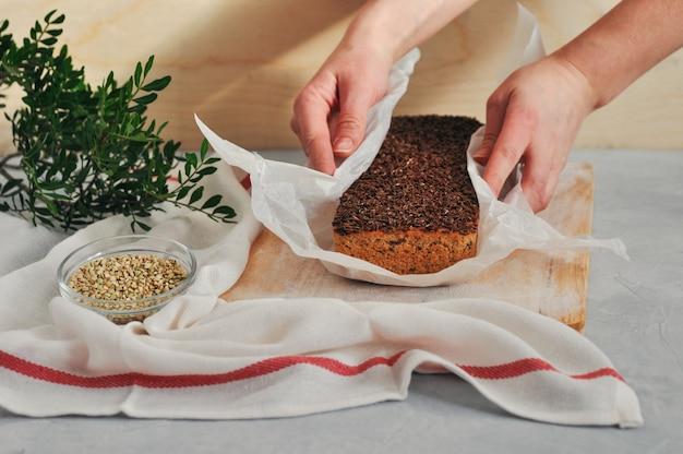 Pane casalingo del vegano su un lievito di grano saraceno verde con i semi di lino, girasole in mani delle donne su un fondo di legno. alimentazione sana e corretta Foto Premium