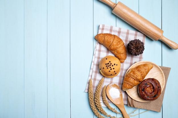Pane fatto in casa o panino, cornetto e mattarello, frusta, farina su legno blu Foto Premium