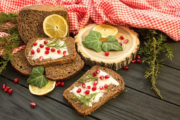 Pane Nero Con Granate Bacche Su Un Fondo In Legno Nero Alimento Di