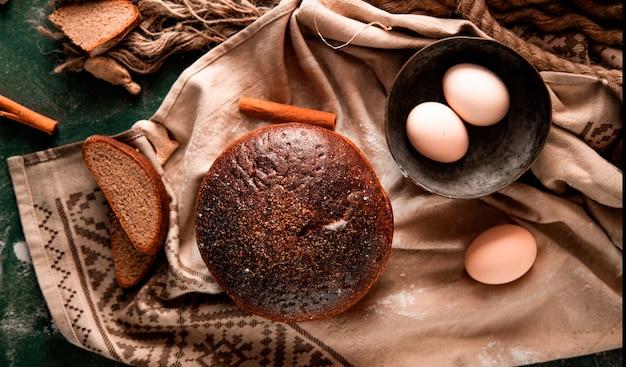 Pane nero rotondo con fette, cannella e ciotola di uova su un tavolo verde. Foto Gratuite