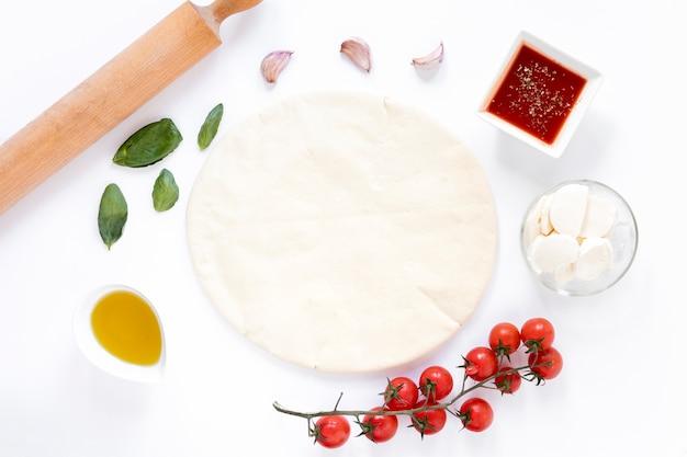Pane piano crudo della pizza ed ingrediente saporito isolati su fondo bianco Foto Gratuite