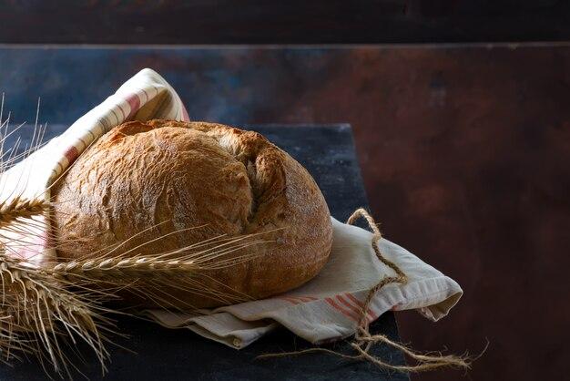 Pane rotondo della segale rustica di recente al forno rotonda con le orecchie del grano e tovagliolo su un'oscurità, copyspace Foto Premium