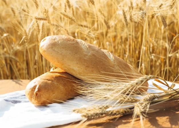 Pane sul tavolo e grano nel campo di grano e giornata di sole Foto Premium
