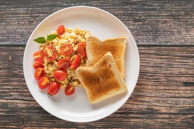 Pane tostato con uova strapazzate e pomodorini Foto Premium