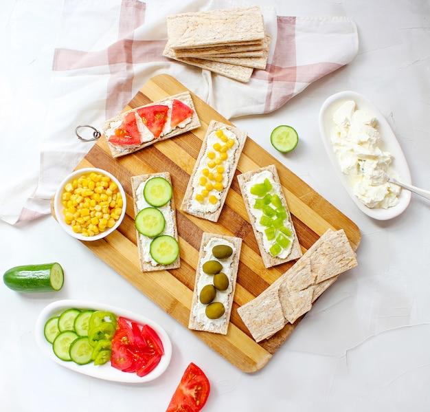 Pane tostato croccante fatto in casa con ricotta e olive verdi, fette di cavolo, pomodori, mais, peperone verde sul tagliere. concetto di cibo sano, vista dall'alto. flat lay Foto Gratuite