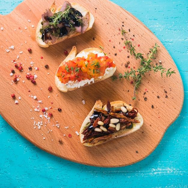 Pane tostato sano della prima colazione con timo; semi di pepe rosso e sale sul tagliere Foto Gratuite