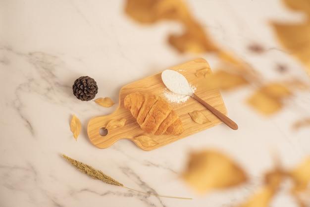 Panetteria fresca, cornetto fresco con cucchiaio pieno di farina su tavola di legno sulla superficie di marmo bianco. gustoso dessert delizioso, colazione francese. vista dall'alto Foto Premium