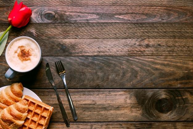 Panetteria sul piatto vicino a tazza di bevanda, fiori e posate Foto Gratuite