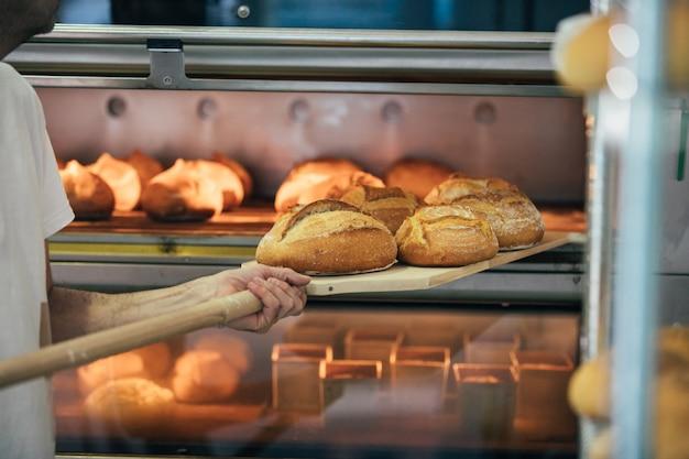 Panettiere che produce pane ad un forno. concetto di panetteria. Foto Premium