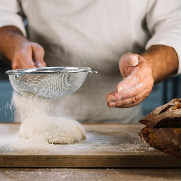 Panettiere che setacciava la farina di frumento attraverso un setaccio d'acciaio sopra l'impasto Foto Gratuite