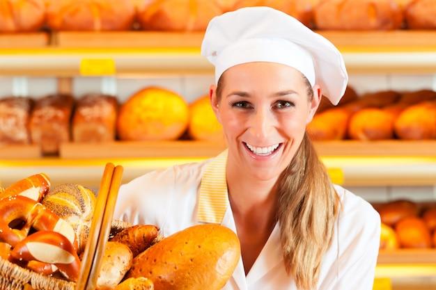 Panettiere femminile nel forno che vende pane dal cestino Foto Premium