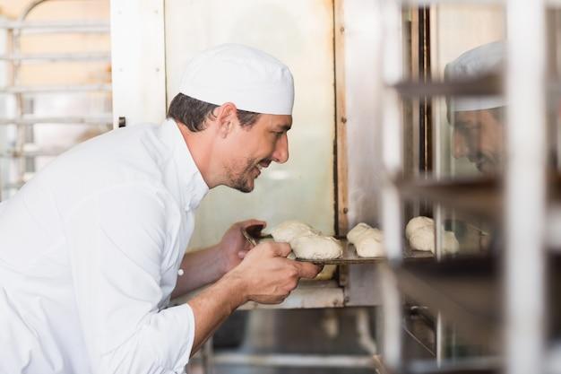 Panettiere sorridente che mette la pasta in forno nella cucina del forno Foto Premium