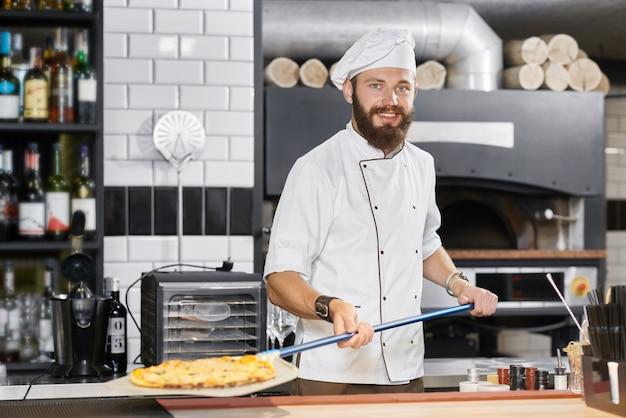 Panettiere sorridente che porta tunica bianca che tiene pala metallica lunga con pizza. Foto Premium