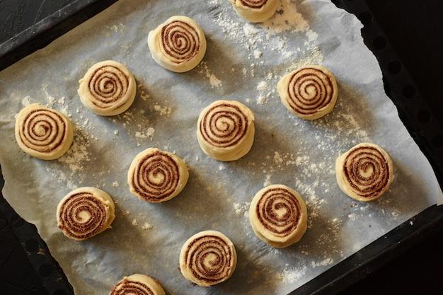 Panini alla cannella - cinnabon processo di cottura cruda pasta.food sfondo Foto Premium