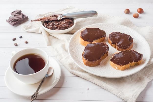 Panini con cioccolato e nocciole sparsi sul piatto. tazza di caffè sul tavolo. Foto Premium