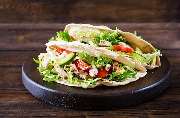 Panini con pane alla griglia con carne di pollo alla griglia, avocado, pomodori, cetrioli e lattuga serviti su legno Foto Premium