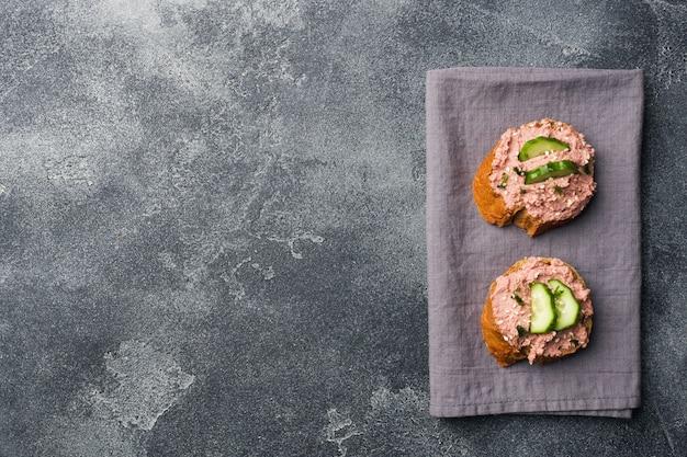 Panini con patè di pollo e cetriolo sul tavolo scuro. Foto Premium