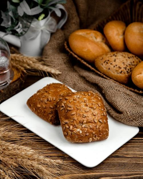 Panini di pane nero con semi di girasole in cima Foto Gratuite