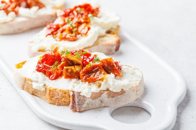 Panini di pomodori secchi e di ricotta sul bordo bianco. Foto Premium