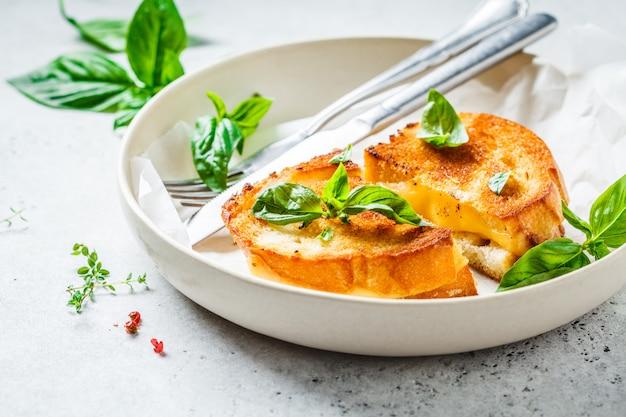 Panini fritti con formaggio e basilico sul piatto bianco. Foto Premium
