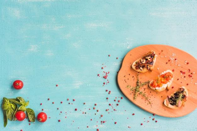 Panini sani tostati con basilico; pomodori e pepe rosso su sfondo colorato Foto Gratuite