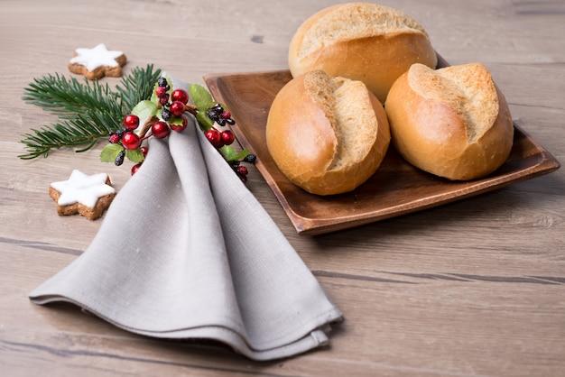 Panini sul piatto di legno con il tovagliolo e le decorazioni di natale Foto Premium