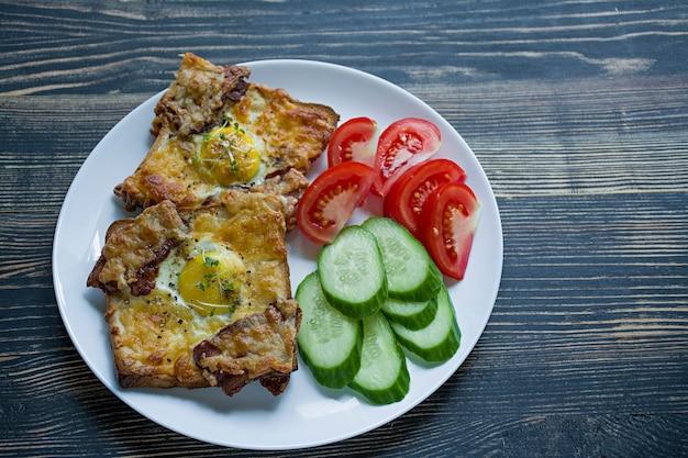 Panino alla griglia con uova, verdure e pancetta su un legno scuro Foto Premium