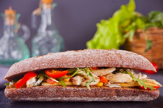 Panino baguette con petto di tacchino, formaggio, lattuga, rucola, pomodori e cipolla su un piatto nero. Foto Premium