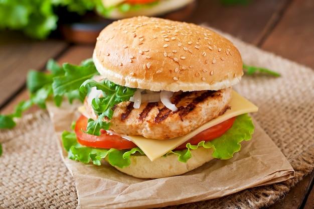 Panino con hamburger di pollo, pomodori, formaggio e lattuga Foto Gratuite